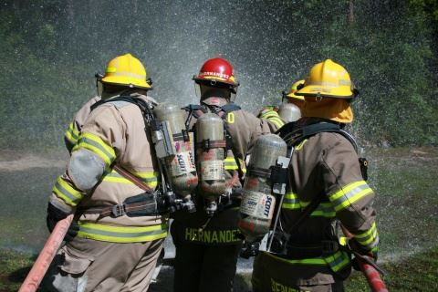 Three Firefighters Spraying Water